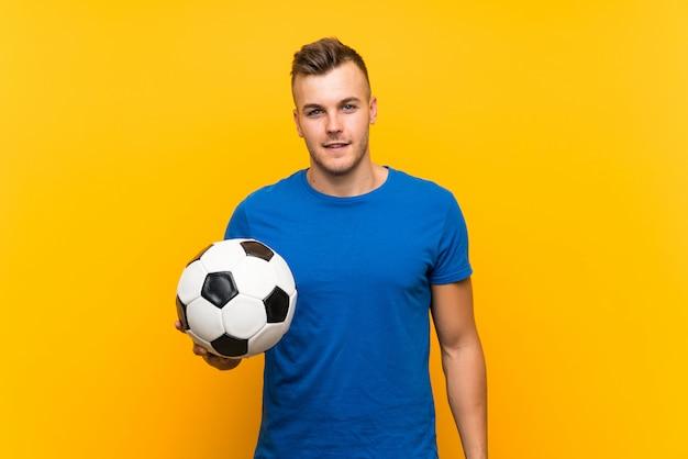 Hombre rubio hermoso joven que sostiene un balón de fútbol sobre la pared amarilla aislada que sonríe mucho