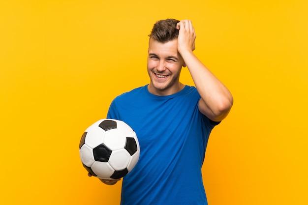 El hombre rubio hermoso joven que sostiene un balón de fútbol sobre la pared amarilla se ha dado cuenta de algo y tiene la intención de la solución