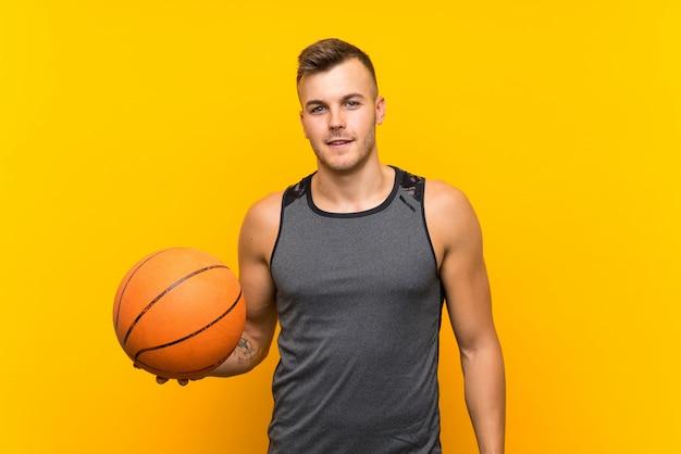 Hombre rubio hermoso joven que sostiene una bola de cesta sobre fondo amarillo aislado que sonríe mucho