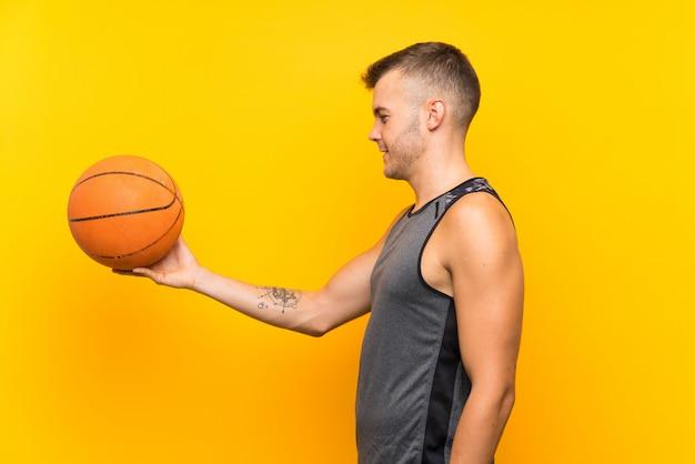 Hombre rubio hermoso joven que sostiene una bola de cesta sobre la pared amarilla aislada con la expresión feliz
