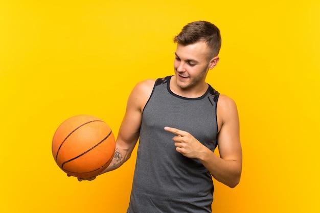 Hombre rubio hermoso joven que sostiene una bola de la cesta sobre la pared amarilla aislada y que lo señala