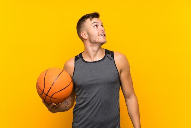 Hombre rubio hermoso joven que sostiene una bola de cesta sobre la pared amarilla aislada que mira para arriba mientras que sonríe