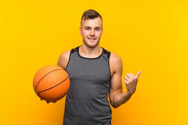 Hombre rubio hermoso joven que sostiene una bola de la cesta sobre la pared amarilla aislada que señala al lado para presentar un producto