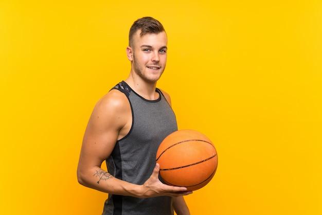 Hombre rubio hermoso joven que sostiene una bola de la cesta sobre la pared amarilla que sonríe mucho