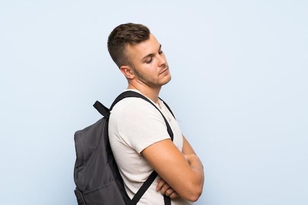 Hombre rubio hermoso joven sobre la pared azul aislada con la mochila