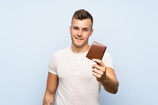 Hombre rubio hermoso joven sobre la pared azul aislada que sostiene una cartera