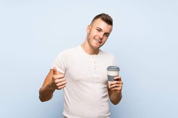 Hombre rubio hermoso joven sobre la pared azul aislada que sostiene la taza de café caliente