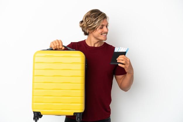 Hombre rubio joven aislado en la pared blanca en vacaciones con maleta y pasaporte