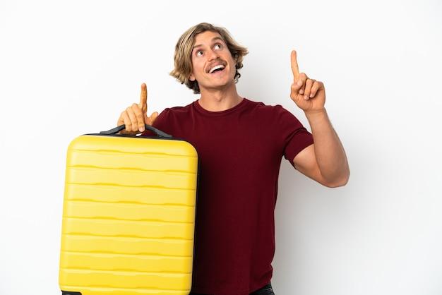 Hombre rubio joven aislado en la pared blanca en vacaciones con maleta de viaje y apuntando hacia arriba