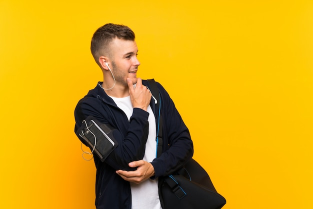 Hombre rubio joven del deporte sobre la pared amarilla aislada que mira el lado