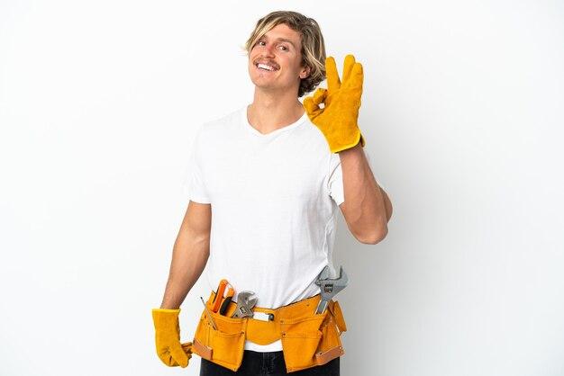 Hombre rubio joven electricista aislado en blanco mostrando signo ok con los dedos