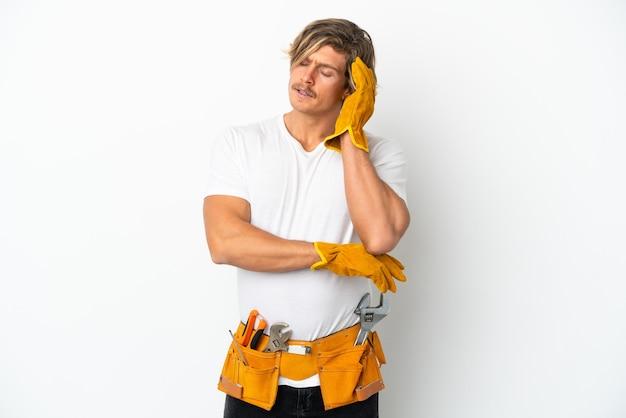 Hombre rubio joven electricista aislado en la pared blanca con dolor de cabeza