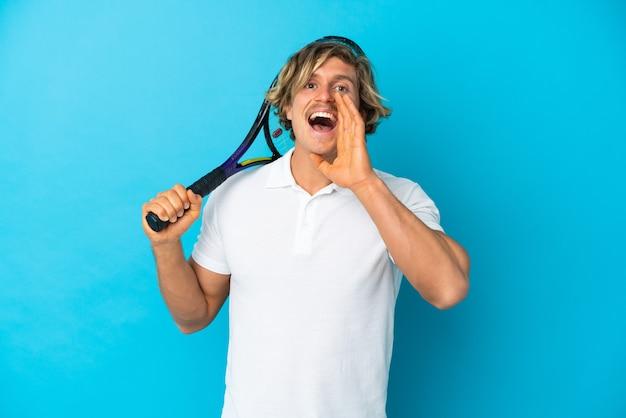 Hombre rubio jugador de tenis aislado en la pared azul gritando con la boca abierta