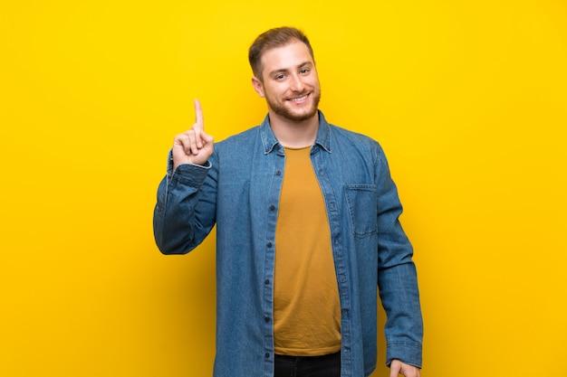 Hombre rubio mostrando y levantando un dedo en señal de lo mejor.