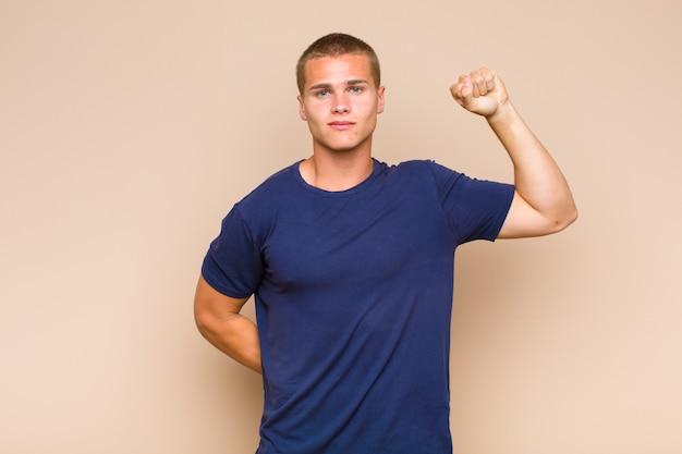 Hombre rubio que se siente serio, fuerte y rebelde, levanta el puño, protesta o lucha por la revolución