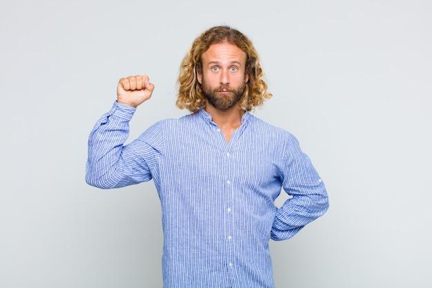 Hombre rubio que se siente serio, fuerte y rebelde, levantando el puño, protestando o luchando por la revolución