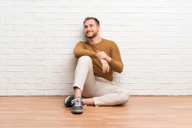 Hombre rubio sentado en el suelo riendo y mirando hacia arriba