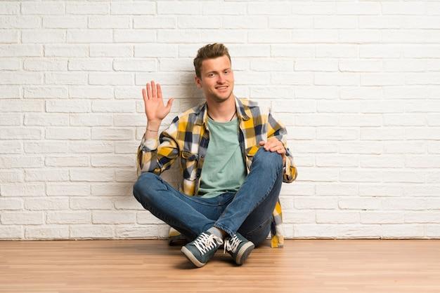 Hombre rubio sentado en el suelo saludando con la mano con expresión feliz