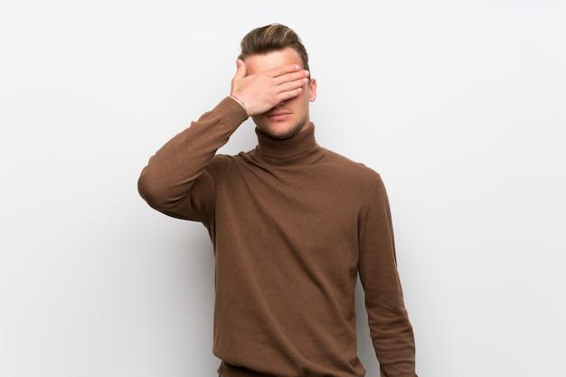 Hombre rubio sobre los ojos blancos aislados del recubrimiento de paredes por las manos. no quiero ver algo