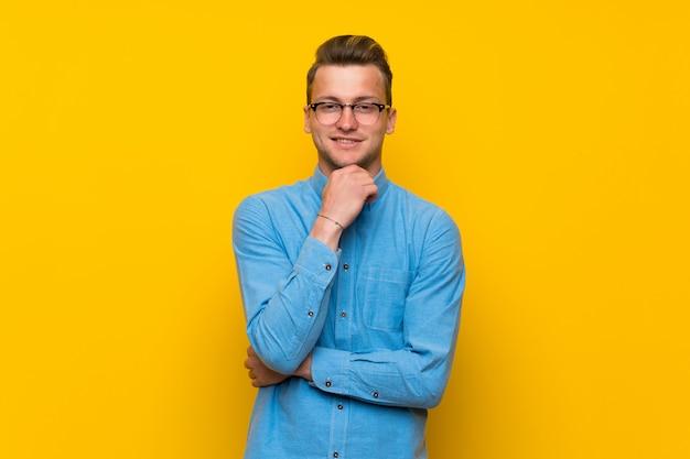 Hombre rubio sobre pared amarilla aislada con gafas y sonriendo