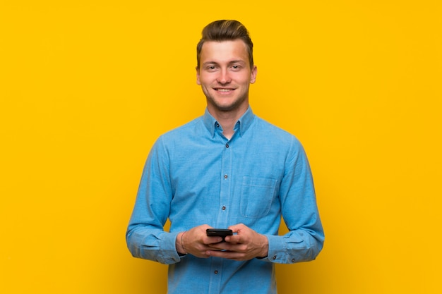 Hombre rubio sobre la pared amarilla aislada que envía un mensaje con el móvil