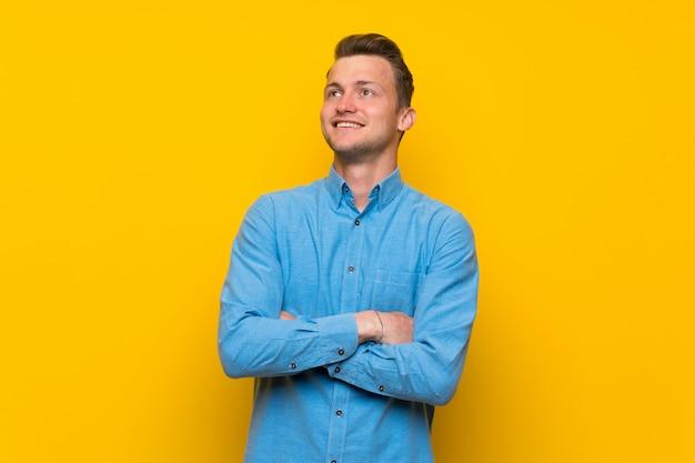 Hombre rubio sobre la pared amarilla aislada que mira para arriba mientras que sonríe