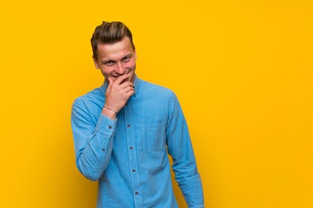 Hombre rubio sobre la pared amarilla aislada que sonríe mucho