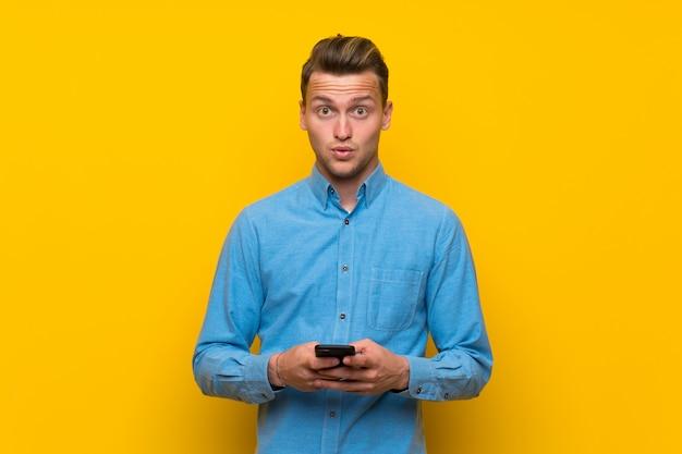 Hombre rubio sobre pared amarilla aislada sorprendido y enviando un mensaje