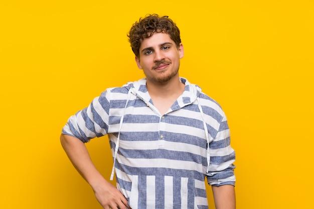 Hombre rubio sobre la pared amarilla que presenta con los brazos en la cadera y la sonrisa