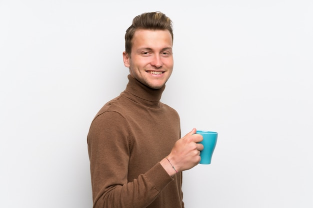Hombre rubio sobre la pared blanca aislada que sostiene una taza de café caliente