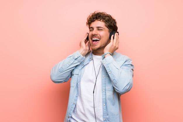 Hombre rubio sobre pared rosa escuchando música con auriculares