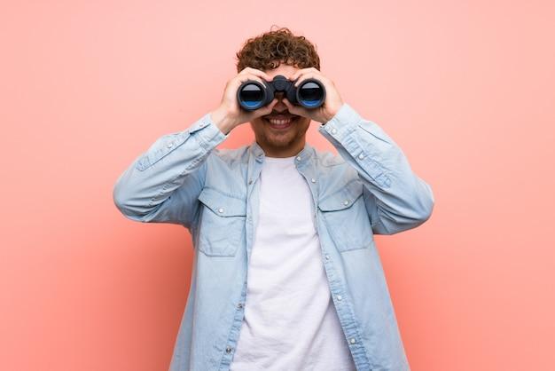 Hombre rubio sobre pared rosa y mirando a lo lejos con binoculares