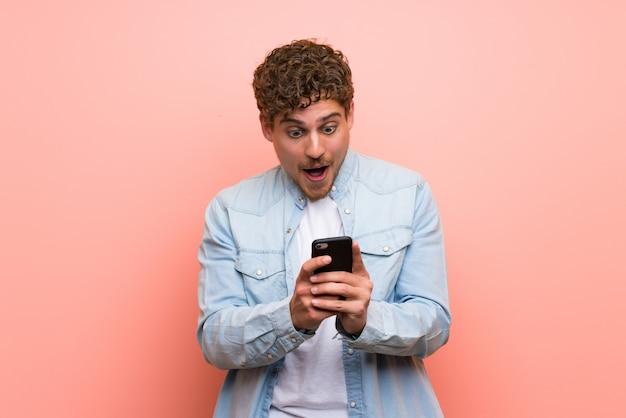 Hombre rubio sobre pared rosa sorprendido con un móvil