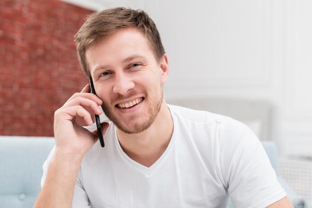 Hombre rubio sonriente hablando por teléfono