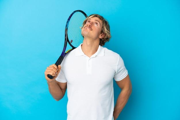 Hombre rubio tenista aislado y mirando hacia arriba