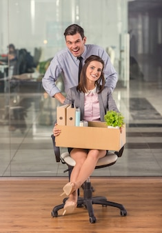 Un hombre rueda a una chica trabajadora en una silla.