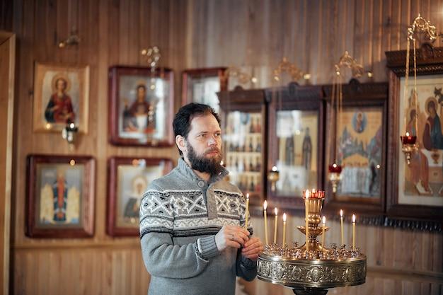 Un hombre ruso con barba se para en una iglesia ortodoxa, enciende una vela y reza frente al icono.