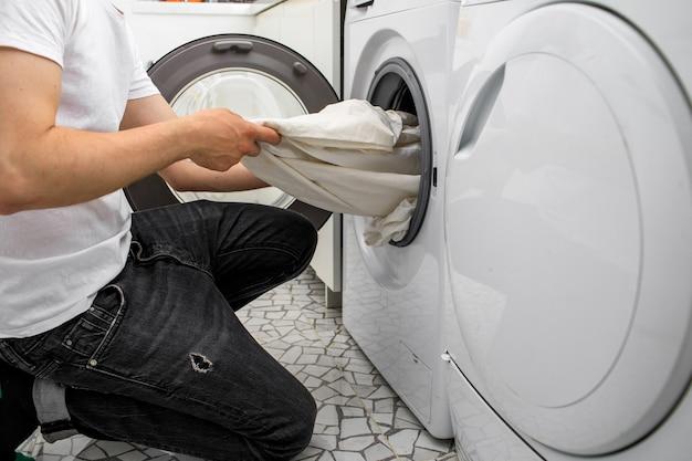 El hombre saca la ropa de una lavadora automática