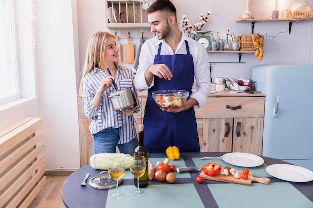 Hombre salado de ensalada mientras que mujer mezcla comida en una olla