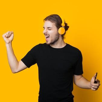 Hombre salido en camiseta negra escuchando música a través de auriculares y bailando en una pared amarilla del estudio
