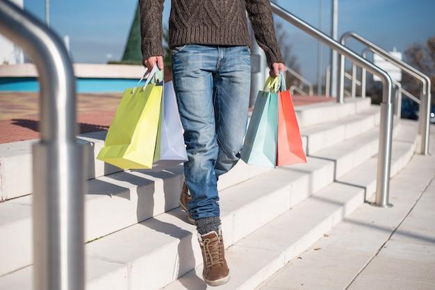 Hombre saliendo de un centro comercial con coloridos bolsos de compras