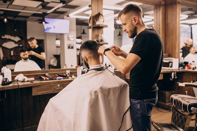 Hombre en un salón de peluquería haciendo corte de pelo y barba