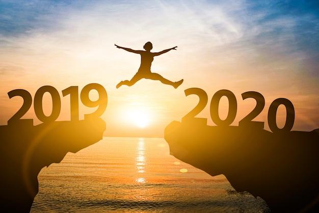 El hombre salta del año 2019 al 2020. a partir del concepto de año nuevo.