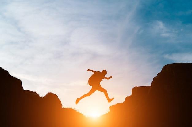 El hombre salta a través de huecos entre colinas