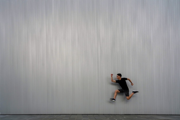 Un hombre saltando en el aire sobre un fondo de textura gris