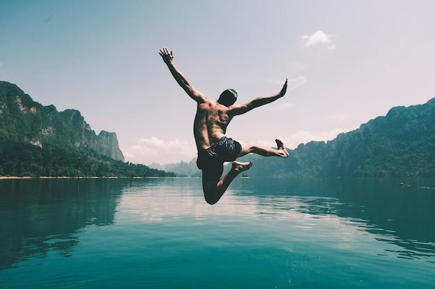 Hombre saltando de alegría por un lago