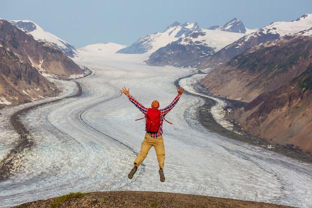 Hombre saltando por encima del glaciar salmon, canadá