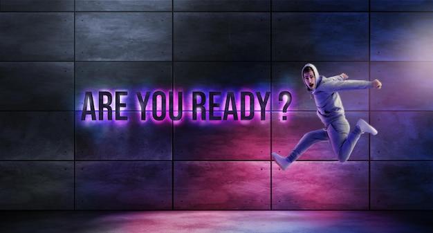Hombre saltando junto a un letrero de neón, ¿estás listo? Foto gratis
