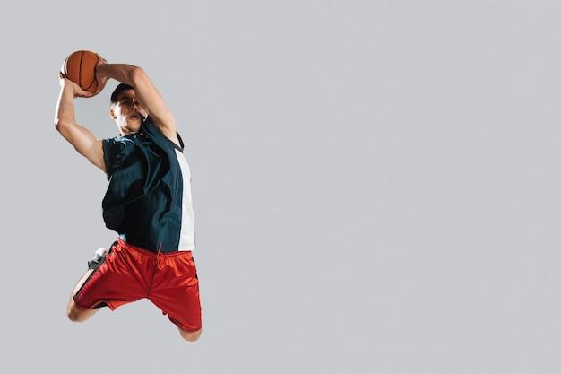 Hombre saltando mientras sostiene una pelota de baloncesto con espacio de copia