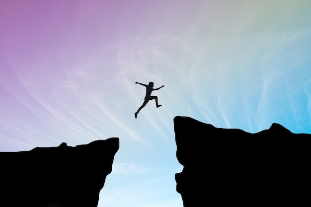 Hombre saltar a través de la brecha entre hill.man saltando sobre acantilado en la puesta de sol de fondo, concepto de concepto de negocio